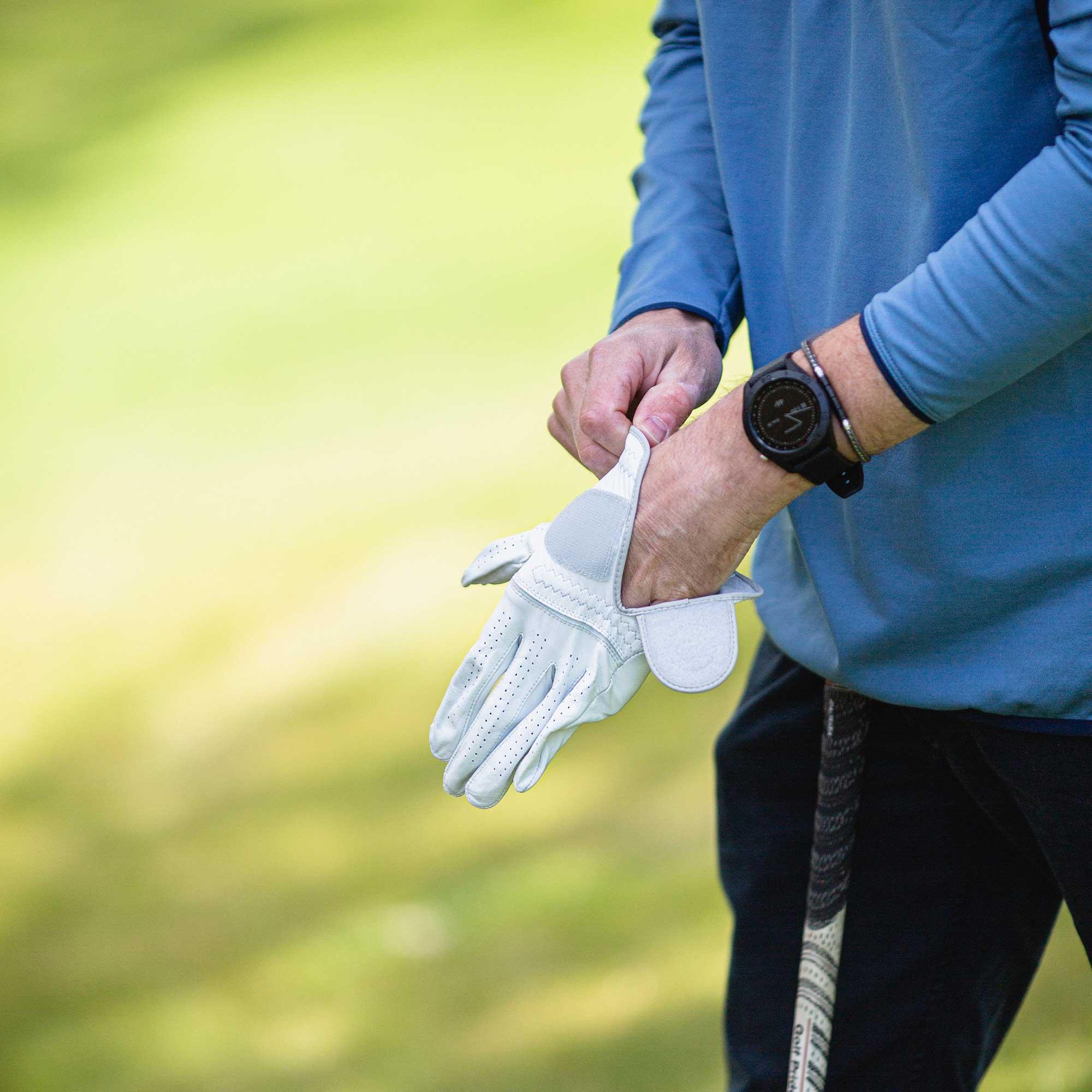 Hand im Golfhandschuh mit Schläger