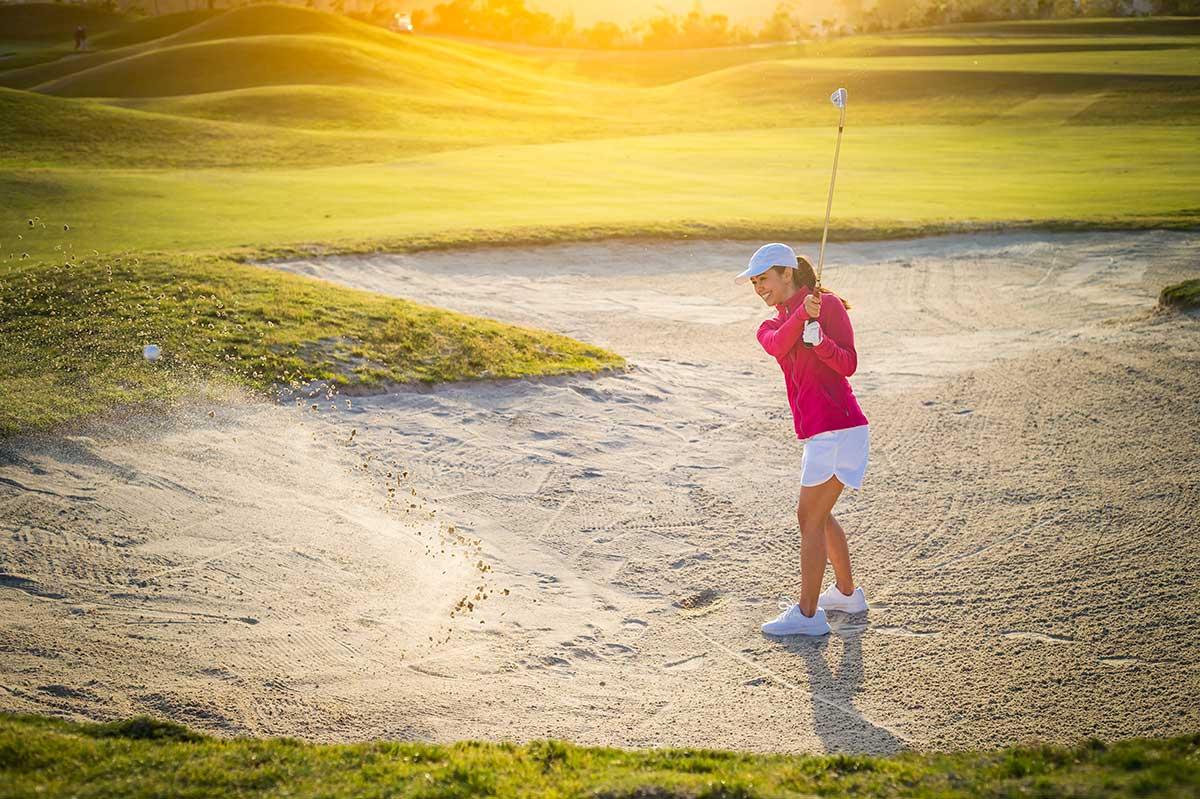 Golferin schlägt aus dem Bunker