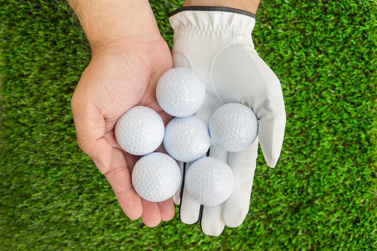 Golfare som håller golfbollar i handen