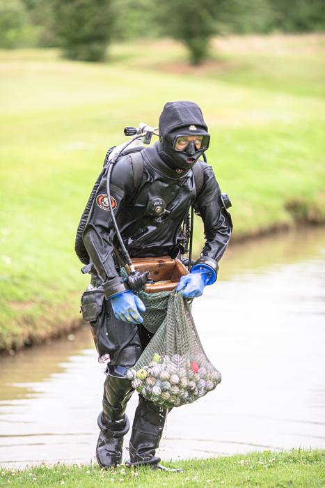 Gående dykker, der bære et net af golfbolde