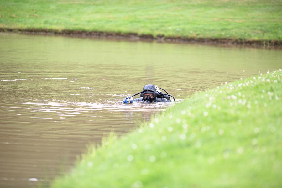 Dykker med tre golfbolde i hånden