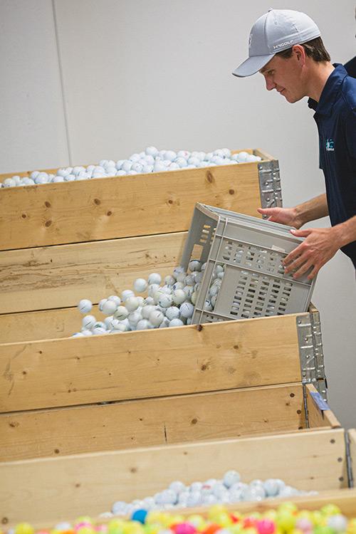 Alexander befüllt große Box mit Golfbällen