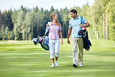 Golfande par som bär på var sin golfbag.