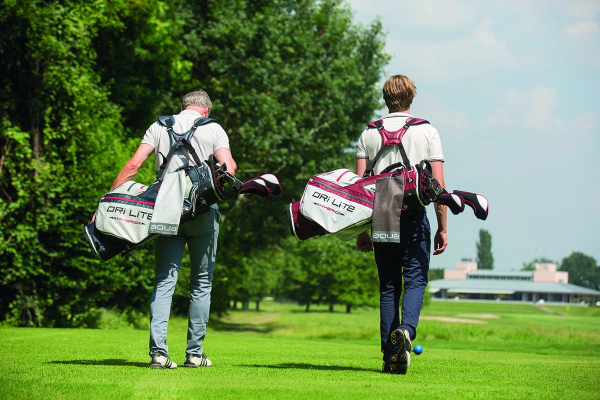 Två golfspelare med bärbagar som går på golfbanan