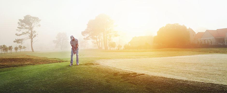 En golfare som chippar mot green med golfbollar och utrustning från Out of Bounds