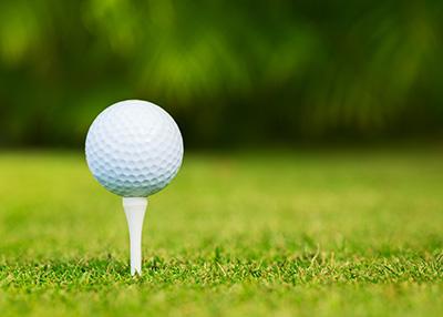 En golfboll som är upp-peggad på tee