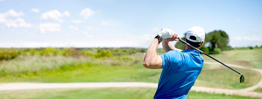 Golfspelare med en golfklocka slår ut från tee