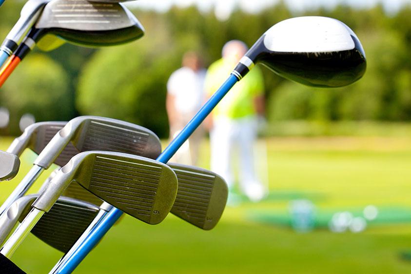 Fokus på golfklubbor med spelare i bakgrunden