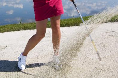 Snygga strumpor på golfspelare som gör ett bunkerslag