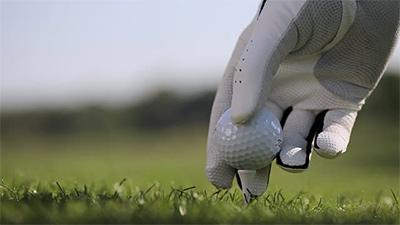 En hand med golfhandske som peggar en golfboll