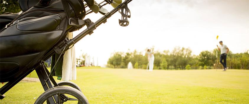 Svart golfbag i fokus. Golfspelare längre bort på green.